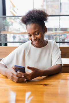 Happy young African American female in white shirt sitting with smartphone in light restaurant with smile