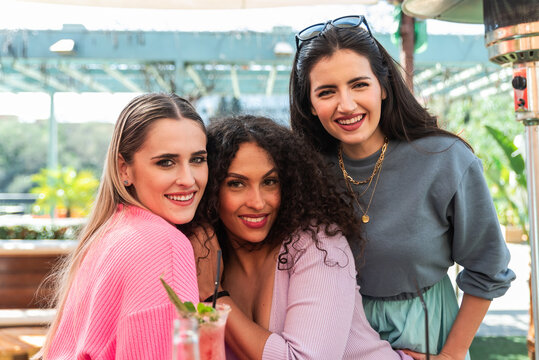 Smiling young multiracial female friends in casual clothes embracing and looking at camera while spending sunny day together on outdoor restaurant terrace