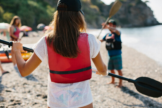 Anonymous people in life jackets standing on sandy seashore and exercising with paddles before kayaking in Malaga Spain