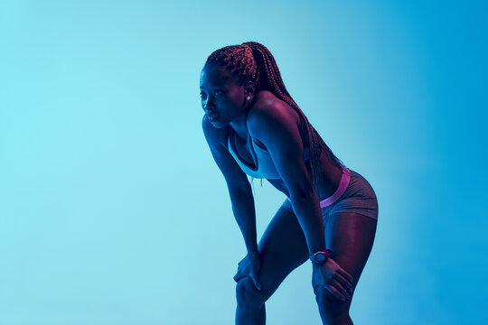 Determined African American female athlete in sportswear touching thighs and looking forward during break from workout in neon light