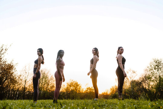 Ground level of group of multiethnic female athletes in sportswear standing on green lawn in park at sundown and looking at camera
