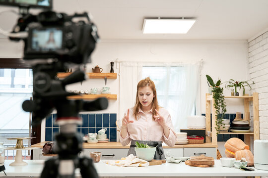 Young female blogger talking against smartphone while recording culinary video and looking down at home