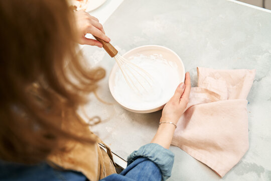 Content young female in apron whipping sweet cream while cooking at table in light house