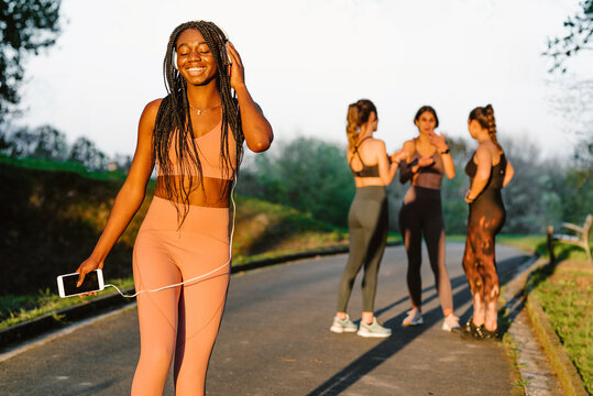 Cheerful African American female athlete listening to music in headphones while standing in park at sunset on background of company of blurred sportswomen