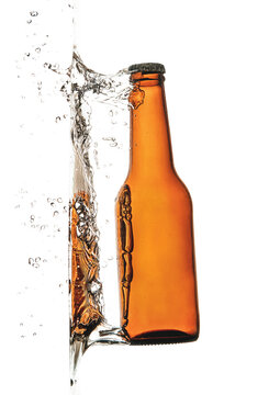 Brown glass bottle with metal lid behind splattering refreshing drink with bubbles in air
