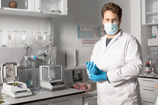 Male chemist in sterile mask and gloves looking at camera against moisture analyzer and analytical balance in cannabis laboratory