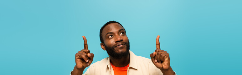 smiling african american man pointing up with fingers isolated on blue, banner - fototapety na wymiar