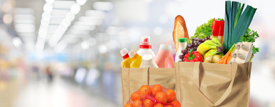 Eco friendly reusable shopping bags filled with different goods on a supermarket background