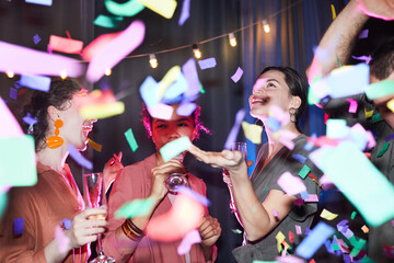 Obraz Diverse group of excited young people dancing under confetti shower with flash - fototapety do salonu