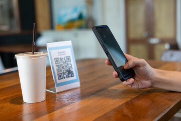 Obraz Men use phones to scan a qr code to select a menu or scan to receive a discount or pay for food and drink inside a cafe. using the phone to transfer money or pay online without cash concept. - fototapety do salonu