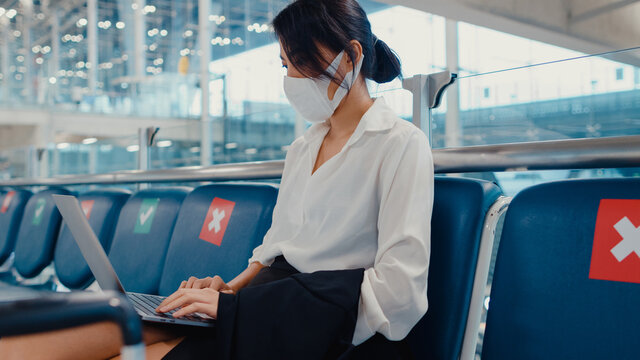 Asian business lady traveller wear face mask sitting in bench use laptop for work between wait for flight in terminal at airport. Business travel commuter in covid pandemic, Business travel concept.