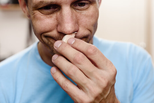 Young sick man smelling garlic while staying at home