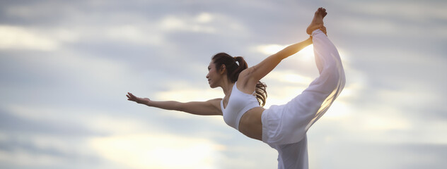 Asian young woman practicing easy yoga poses for beginners. Exercise while looking out to the sky. Stretching and Strengthening Exercises with yoga. Banner size with copy space.