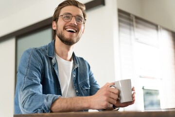 Young casual man with mug of tea or coffee in kitchen.