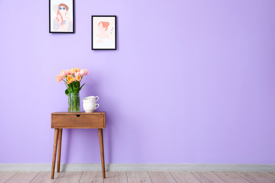 Bouquet of tulip flowers on wooden table near color wall