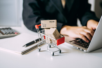 Fototapeta card box small in shopping cart with businesswomen using laptop on a desk, e-commerce, and delivery online business concept. obraz
