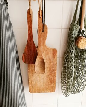 Apron And Utensils Hanging Against Wall At Home