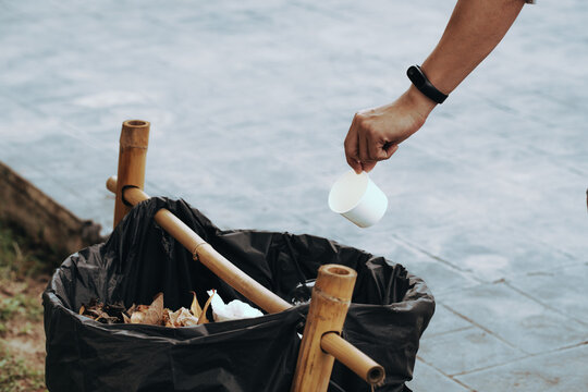 Cropped Hand Of Woman Throwing Disposable Cup In Garbage