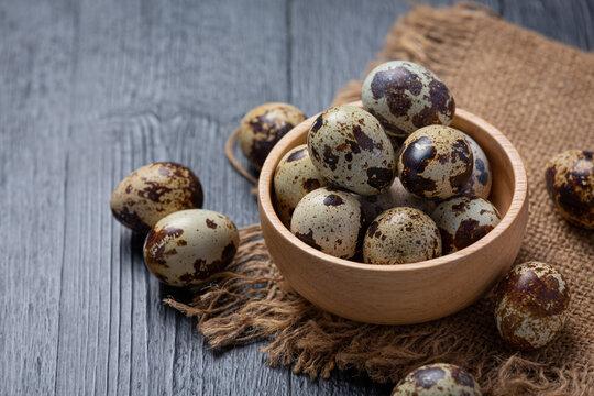 fresh quail eggs on the dark wooden background.