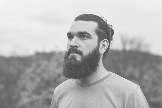 Black and white portrait of bearded hipster man outdoors, serious man