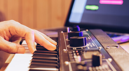 male musician hand playing midi keyboard for arranging music on laptop computer. music production...