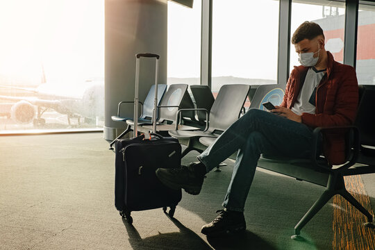 Man wearing a mask waiting his flight at the gate in the airport