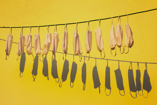 Close-up Of Clothes Drying On Clothesline Against Yellow Wall