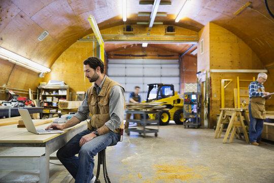 Carpenter using laptop in workshop