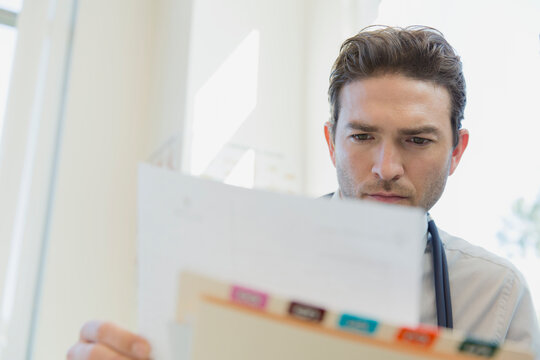 Mid adult male doctor reviewing medical records in clinic