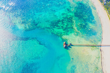 Aerial view of Maldives island, luxury water villas resort and wooden pier. Beautiful sky and ocean lagoon beach background. Summer vacation holiday and travel concept. Paradise aerial landscape pano - fototapety na wymiar