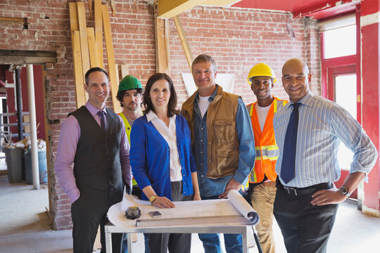 Portrait of team of architects and tradesmen standing at construction site
