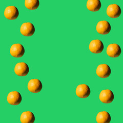 Fruit pattern made of fresh oranges on green pastel background. Top view. Copy space. Pop art design, creative summer concept.