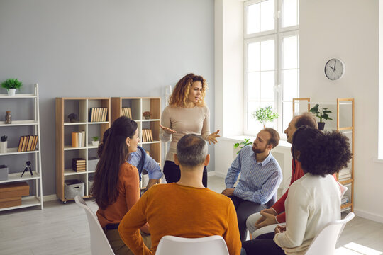 Group therapy. Different people sit in a circle at a support group meeting and listen to a woman who shares her problem. During communication, people listen to each other's stories.