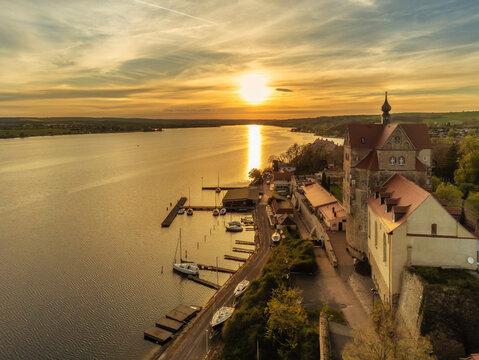 Schloss Seeburg am Süßen See in Sachsen-Anhalt bei Sonnenuntergang mit Blick auf die Bootsanleger