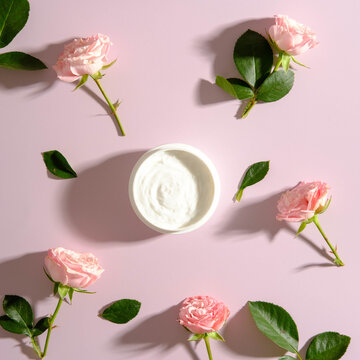Jar of moisturizer cream and rose flowers on pink backrground. SPA roses cosmetics concept.