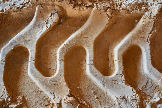 tractor wheel imprint on the compacted sand of a construction site