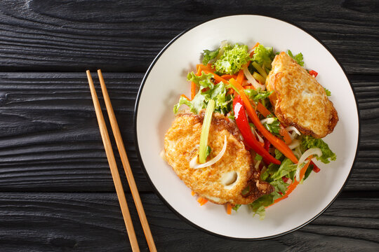 Asian salad of fried eggs with vegetables and herbs close-up in a plate on the table. horizontal top view from above