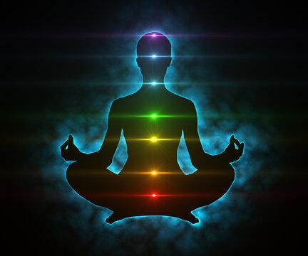 Glowing aura and chakras on meditating figure in yoga lotus pose