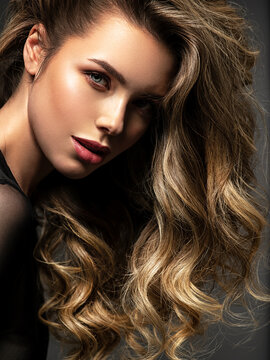Portrait of a  beautiful woman with a long hair. Pretty blonde girl with curly hairstyle.