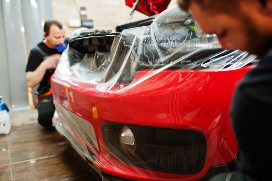 Car service worker put anti gravel film on a red car body at the detailing vehicle workshop. Car protection with special films.