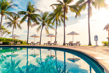 Beautiful luxury umbrella and chair around outdoor swimming pool in hotel and resort with coconut...