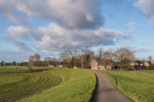 landscape with biking road on dike with farm and little village in the Dutch polder near river IJssel