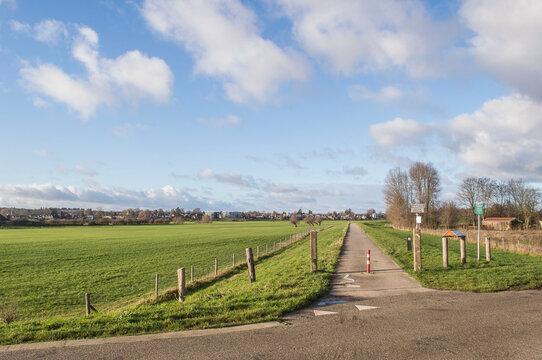 biking road on dike near river IJssel in Dutch polder in winter