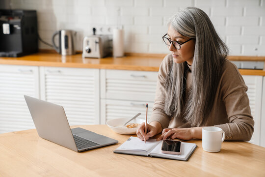 Mature grey woman writing down notes while working with laptop