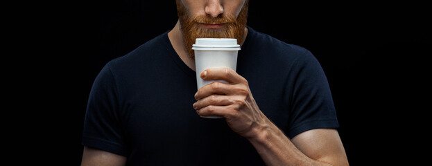 Fototapeta Croped shot of young caucasian bearded stylish man with paper cup of coffee to go over black background. Coffee to go concept. obraz