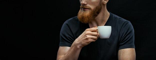 Obraz Croped shot of bearded man drinking coffee. Resting man drinking espresso coffee holding cup of coffee in hand. Studio shot on black background wit copy space on left - fototapety do salonu