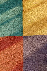 Obraz Junction of four multi-colored squares of floor covering with long shadows. Padded floor covering with rubber granules. Special rubber coating for the playground or sports activity. - fototapety do salonu