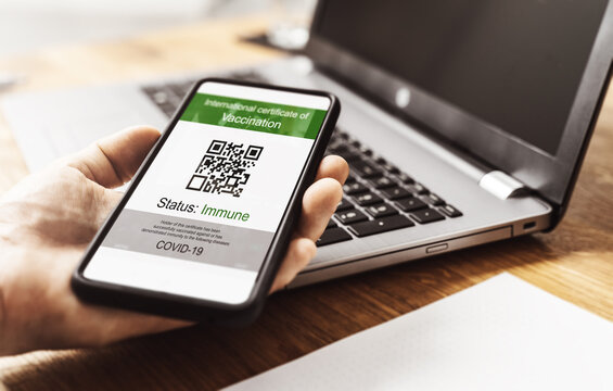 digital vaccination passport and health certificate on smartphone is held in hand in front of a notebook at home. digitaler impfpass at smartphone