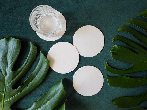 Blank white coasters isolated on dark green velvet fabric