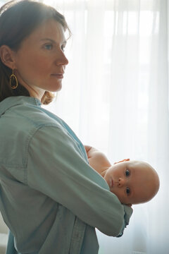 Side view of loving mother standing with adorable infant in room at home